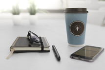 coffee mug, reading glasses, journal, cellphone, and pen
