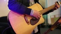 strumming a guitar during a worship service