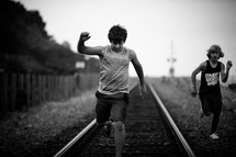 boys running on train tracks