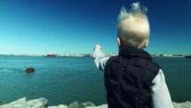 little boy pointing out at the water on a shore