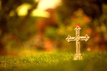 a gold cross in grass