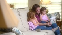 mother and daughters reading a children's Bible together