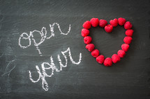 word open your in chalk and raspberries in the shape of a heart