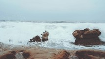 waves crashing into rocks along a shore