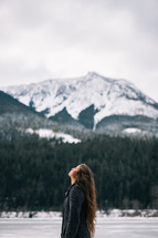 a woman standing outdoors in winter looking up