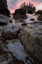 tide washing over rocks forming tide pools at sunset