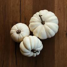 white pumpkins on a wood floor