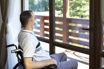 a man in a wheelchair looking out a window