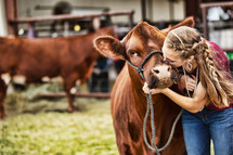Girl kissing her heifer at a county fair competition.