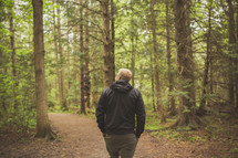a man walking alone in a forest