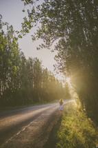 Woman walking down a rural road under sunlight