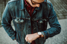 a young man in a jean jacket looking down at his watch