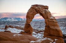 Delicate Arch in Utah taken with snow on it right after sunset.