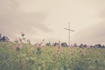 a cross in a field on flowers