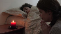 a mother praying next to her sleeping son