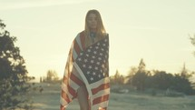 Young Woman Wrapped in American Flag Walks Toward Camera in Slow Motion