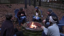 friends sitting by a fire pit