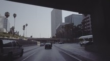 Traveling through downtown Los Angeles passing tall buildings and overpasses.