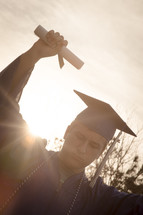 graduate holding up his diploma