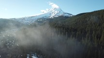 snow capped mountain peak and low hanging clouds