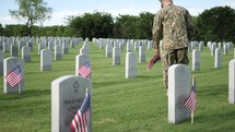 soldier placing flags at grave sites at Arlington National Cemetery