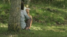 woman sitting under a tree reading from a journal