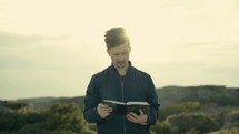 man standing on a mountaintop reading a Bible