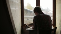 a man sitting at a desk in front of a window reading a Bible