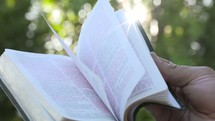 man flipping through the pages of a Bible