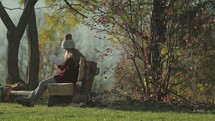 a girl sitting on a bench outdoors reading a Bible