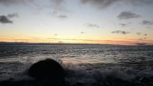 waves washing onto a shore at dusk