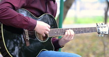 Close up person man's hands playing acoustic guitar artist musician outdoors.  Worship concept.