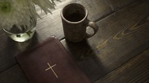 coffee mug, Bible, and vase of flowers on a table in front of a window