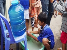 a child washing his hands in clean water