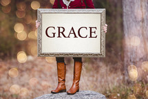a woman holding a sign the reads grace