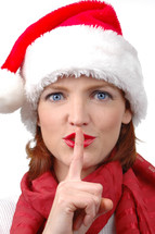 "A woman in a Santa hat with her finger to her lips saying ""sshhh."""