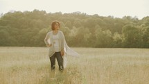 carefree woman walking through a field
