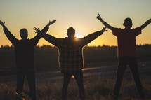 young men with hands raised at sunset