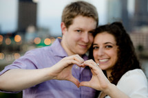 Happy couple making heart shape with hands
