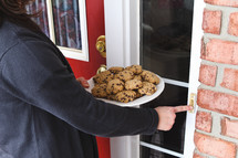 a woman ringing a doorbell and bringing cookies to a neighbor
