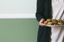 a torso of a woman holding a plate of cookies
