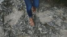 woman in sandals walking down a rock slope