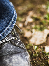a boot and jeans standing on the ground in a forest