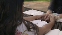 friends holding hands praying at a Bible study outdoors