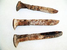 A set of three old, rusty and weather torn steel nails like the ones used to crucify Jesus and nail His hands and feet to the cross.