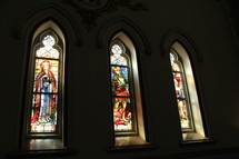 A set of three Stained glass windows in a historic church sanctuary that is over 200 years old in a historic city in the southeastern United States.