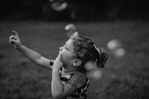 a little girl chasing bubbles