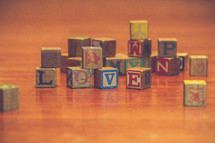 a pile of wood blocks on a playroom floor and the word love