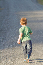 boy child walking on a gravel road
