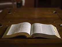 Bible laying open on a wooden table.